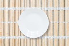 Close-up witte ceramische schotel op houten mat geweven achtergrond op eettafel in hoogste mening Stock Fotografie