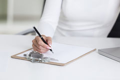 Close up of woman's hands and clipboard Stock Photography