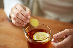 Close up of woman adding ginger to tea with lemon. Health, traditional medicine and ethnoscience concept - close up of woman adding ginger to tea cup with lemon stock photo