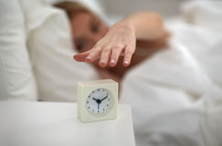 Close up of woman with alarm clock in bed at home Royalty Free Stock Images
