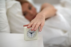 Close up of woman with alarm clock in bed at home Royalty Free Stock Photography