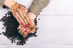 Close-up of a woman applying coffee scrub to her hands. Top view Royalty Free Stock Image