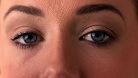 Close up of woman applying eye shadow to eye stock footage