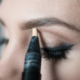 Close Up of Woman Applying Make Up Along Brow Line Stock Image