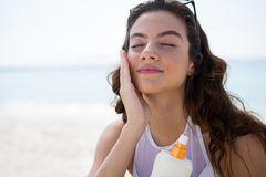 Close up of woman applying sunscream on face. Close up of woman with eyes closed applying sunscream on face Royalty Free Stock Photos