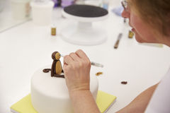 Close Up Of Woman In Bakery Making Monkey Cake Decoration Royalty Free Stock Image