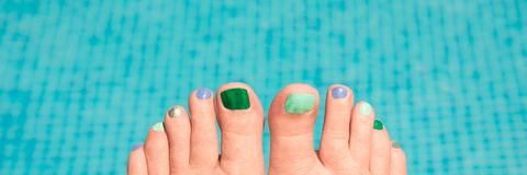 Close up on woman bare feet, water in the background Stock Images