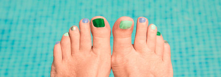 Close up on woman bare feet, blue water in the background Stock Image