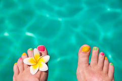 Close up on woman bare foot, turquoise swimming pool. Water in the background Stock Images