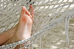Close up on woman bare foot in white hammock Stock Photo