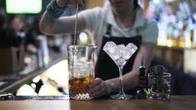 Close up of a woman bartender stirring ice in a jug stock footage