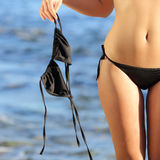 Close up of a woman on the beach in topless holding the bikini bra. With the blue water in the background Royalty Free Stock Image