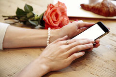 Close-up of woman beautiful hands holding mobile phone. Blank phone screen for layout. Red roses flowers behind on wooden table. S Stock Image