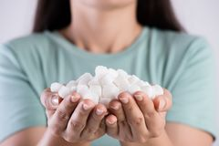 Close up woman beautiful hands holding white sugar cubes. Healthcare concept.  stock photography