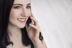 Close up of woman in beige on phone Stock Photo