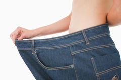 Close-up of a woman belly in too big pants Royalty Free Stock Image