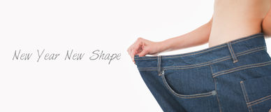 Close up of a woman belly in too big pants. Against white background Royalty Free Stock Image