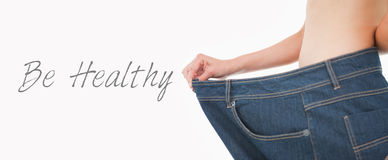 Close up of a woman belly in too big pants. Against white background Royalty Free Stock Photos