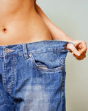 Close-up of woman belly in a too big pants stock photography