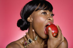 Close up of woman biting an apple over colored background Royalty Free Stock Photography