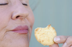 Close up woman biting sweet cookie snack closed eyes Stock Images