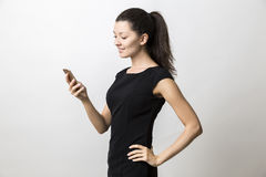 Close up of woman in black dress is looking at her cell phone sc Royalty Free Stock Image