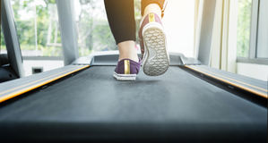 Close up woman in black sportswear running on treadmill machine stock photos