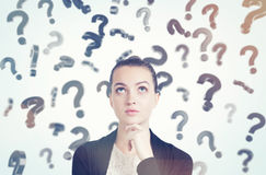 Close up of woman in black and white clothes and floating question marks on sunny day. Close up of thoughtful young woman with her hand on the chin standing in royalty free stock photo