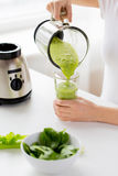Close up of woman with blender jar and green shake Stock Images