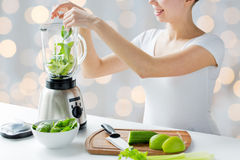 Close up of woman with blender and vegetables Stock Photo