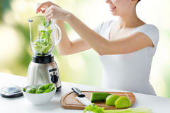 Close up of woman with blender and vegetables Stock Photos