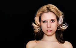 Close-up of a woman with blonde curls on a dark background royalty free stock photos
