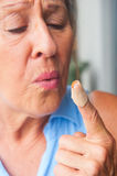 Close up Woman blowing band aid finger wound Royalty Free Stock Photos