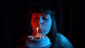 Close Up Of A Woman Blowing Out Candle On Cake Black