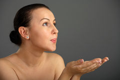Close-up woman blowing in their own hands Royalty Free Stock Photography