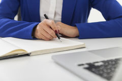 Close up of woman in blue blazer is taking notes at a table Royalty Free Stock Images