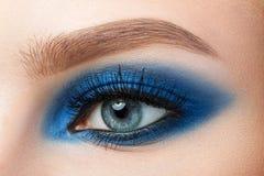 Close-up of woman blue eye with beautiful blue smokey eyes makeu. P. Modern fashion make-up Royalty Free Stock Photography