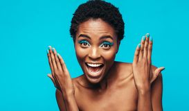 Excited female model showing her vivid makeup. Close up of woman with blue eye shadow and nail paint against blue background. Excited female model showing her Stock Photography