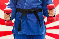 Close Up of Woman in Blue Judo Gi, and Black Belt, which is Trai Royalty Free Stock Photo