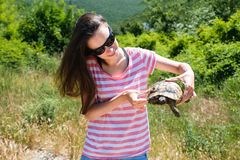 Close-up woman brunette in sunglasses and striped t-shirt keeping turtle in her hands in the forest stock images