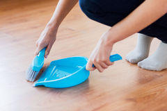 Close up of woman with brush and dustpan sweeping Royalty Free Stock Photography
