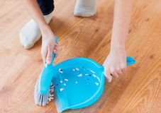 Close up of woman with brush and dustpan sweeping Stock Photography