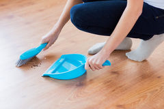 Close up of woman with brush and dustpan sweeping Royalty Free Stock Images