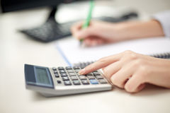 Close up of woman with calculator taking notes Royalty Free Stock Images