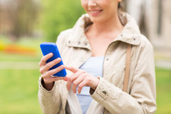 Close up of woman calling on smartphone in park Stock Image