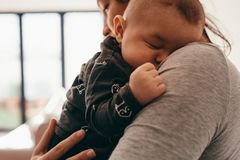 Close up of a woman carrying her sleeping baby stock images
