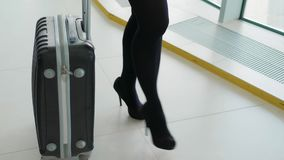Close up of woman carrying suitcase at the airport terminal and hurry up for check in on holiday or business trip. Happy. Close up of woman carrying suitcase at stock footage
