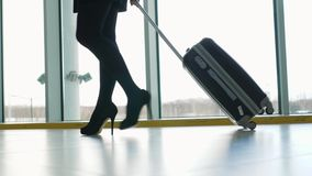 Close up of woman carrying suitcase at the airport terminal and hurry up for check in on holiday or business trip. Happy. Close up of woman carrying suitcase at stock video