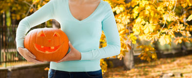 Close up of woman with carved halloween pumpkin Stock Images