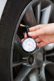 Close-Up Of Woman Checking Car Tyre Pressure With Gauge Royalty Free Stock Photo